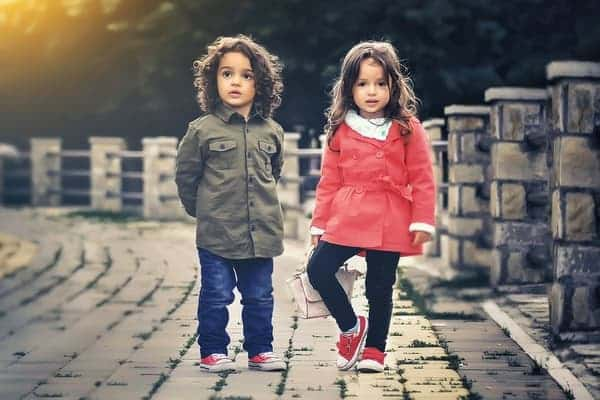 Photo of two cute kids standing on a bridge whose parents are pursuing financial independence